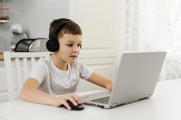 Junge ein haus, das auf laptop spielt und kopfhörer trägt