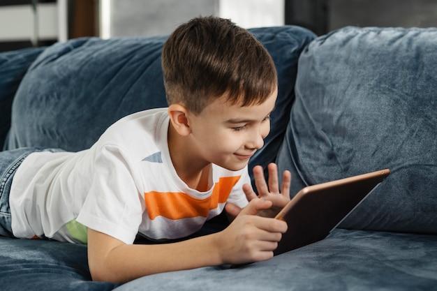 Junge ein haus, das jemandem auf digitalem tablett winkt