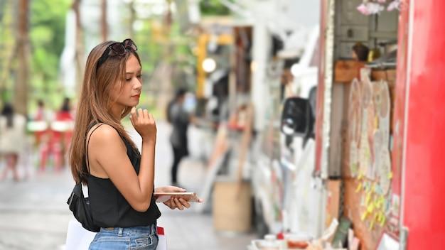 Junge einkaufsfrau, die auf lebensmittel-lkw im park, lebensmittelstraßenkonzept wartet und schaut.