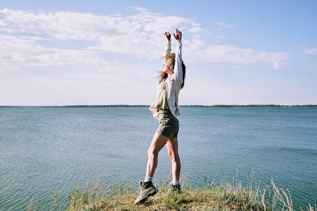 Junge ekstatische frau mit erhobenen armen, die augen geschlossen halten, während sie am flussufer am wasser stehen und einsamkeit genießen