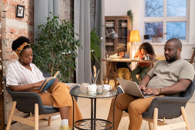 Junge elegante afrikanische frau liest ein buch und ihr ehemann vernetzen sich an einem kleinen tisch, während ihre beiden kinder hausaufgaben im hintergrund machen