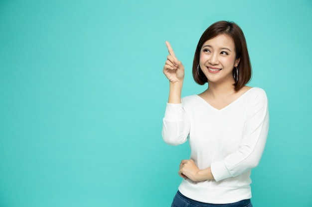 Junge elegante asiatische frau, die lächelt und auf leeren kopienraum lokalisiert auf grüner wand zeigt