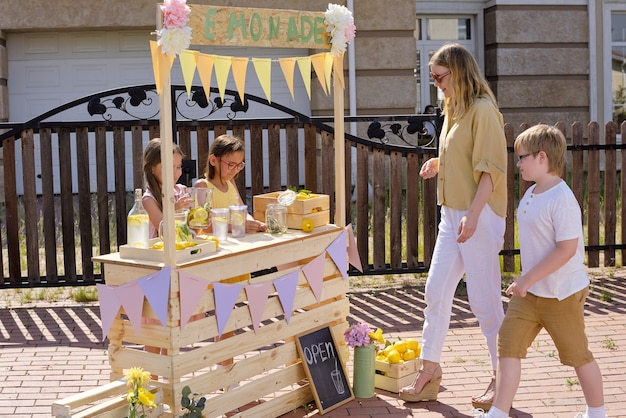 Junge elegante blonde frau und ihr kleiner sohn kommen zum hölzernen stand, wo zwei niedliche mädchen frische kühle hausgemachte limonade verkaufen