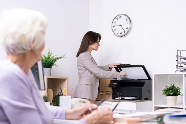 Junge elegante büro-sekretärin oder versicherungsvertreterin, die kopie des dokuments für älteren kunden macht, während sie zur xerox-maschine steht