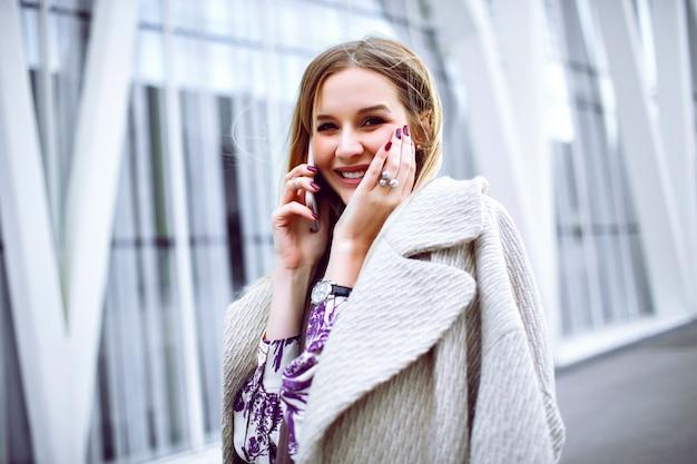 Junge elegante dame, die auf ihrem smartphone anruft und einen trendigen beigen luxusmantel, einen taupefarbenen kaschmirschal und ein blumenkleid trägt und in der nähe des geschäftszentrums des modells posiert.