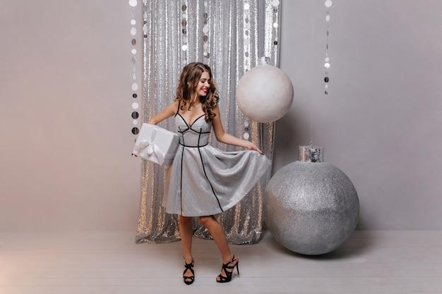 Junge, elegante dame in high heels hält box mit neujahrsgeschenk und berührt kokett ihr brillantes prächtiges kleid