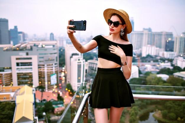 Junge elegante frau, die modisches trendiges sommeroutfit trägt, das touristisches selfie an der terrasse des luxushotels macht