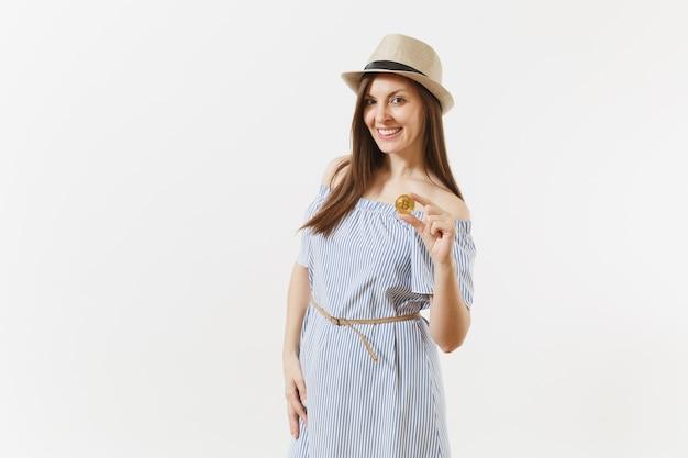 Junge elegante frau im blauen kleid, hut mit dem langen haar, das bitcoin-münze der goldenen farbe lokalisiert auf weißem hintergrund hält. finanzen, virtuelles online-währungskonzept für unternehmen. werbefläche. platz kopieren