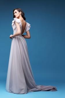 Junge elegante frau im langen rosa kleid. eleganter stoff, abend, hochzeitskleid.