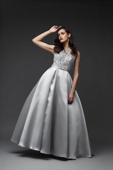 Junge elegante frau im langen silbernen kleid. eleganter stoff, abendkleid.