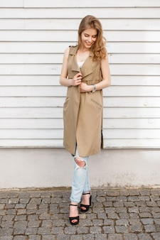Junge elegante frau in einer beige weste in einem weißen t-shirt in stilvollen blauen zerrissenen jeans in schwarzen sandalen mit einer schwarzen handtasche steht in der nähe einer hölzernen weißen vintage-wand. nettes europäisches mädchen auf einem spaziergang