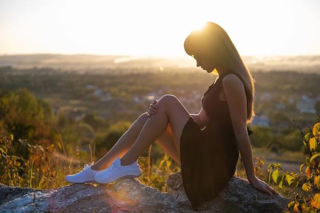 Junge elegante frau in schwarzem, kurzem kleid und weißen turnschuhen, die auf einem felsen sitzen und sich am sommerabend im freien entspannen. modische dame, die warmen sonnenuntergang in der natur genießt.