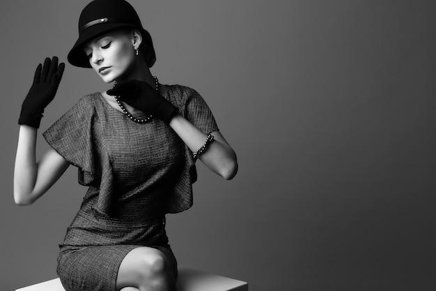Junge elegante frau, retro-mode, hut, handschuhe, kleid. schwarzweiss-bild.