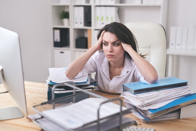 Junge elegante geschäftsfrau, die ihren kopf berührt, während sie computerbildschirm mit missverständnissen beim arbeiten im büro betrachtet