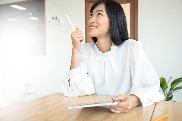 Junge elegante geschäftsfrau im weißen hemd und im ralax am zusammenarbeitenden raum mit tablette im café. träumen positiv denkendes personenkonzept.