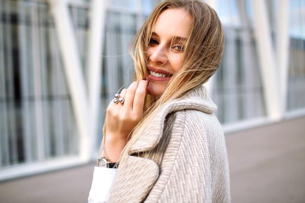 Junge elegante hübsche blonde frau posiert auf der straße, natürlicher sinnlicher blick, lächelt und schaut vor der kamera, trägt trendigen beigen mantel und luxusaccessoires, frühlingsherbstzeit, weiche farben.