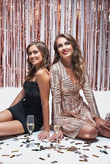 Junge elegante mädchen, die spaß haben und champagner während der party des neuen jahres trinken.