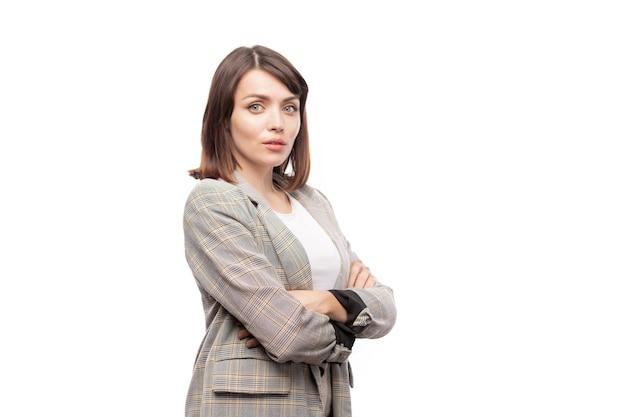 Junge elegante sekretärin oder lehrerin im anzug, die ihre arme auf der brust verschränkt, während sie isoliert steht