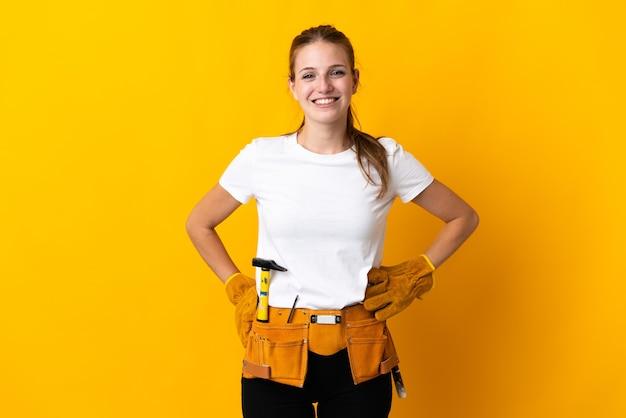 Junge elektrikerfrau lokalisiert auf gelbem hintergrund, der mit den armen an der hüfte aufwirft und lächelt