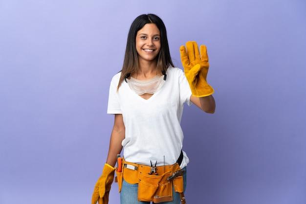 Junge elektrikerfrau lokalisiert auf lila hintergrund glücklich und zählt vier mit den fingern