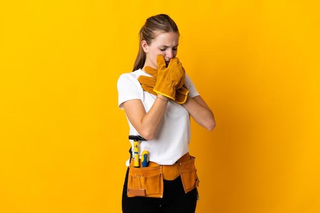 Junge elektrikerin, die auf gelber wand isoliert wird, leidet mit husten und fühlt sich schlecht