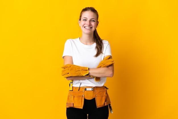 Junge elektrikerin lokalisiert auf gelb, die die arme in frontalposition gekreuzt hält