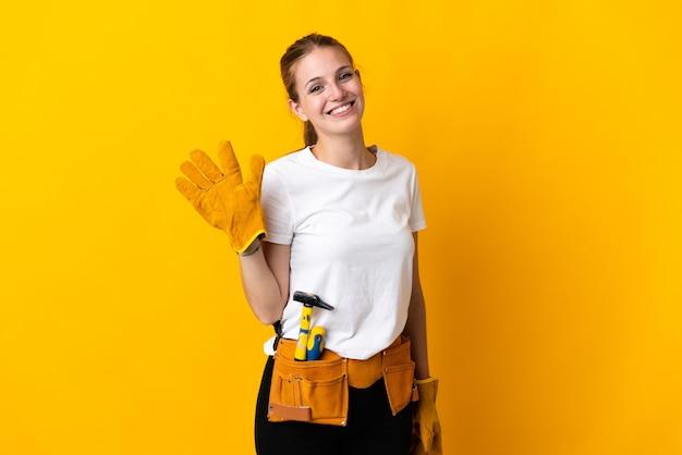 Junge elektrikerin lokalisiert auf gelbem gruß mit hand mit glücklichem ausdruck