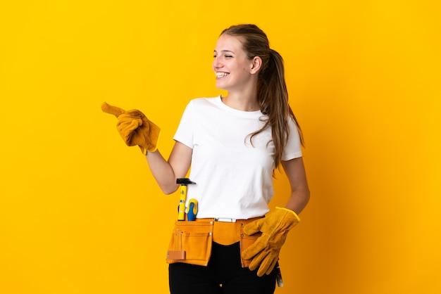 Junge elektrikerin lokalisiert auf gelbem hintergrund, der finger zur seite zeigt und ein produkt präsentiert
