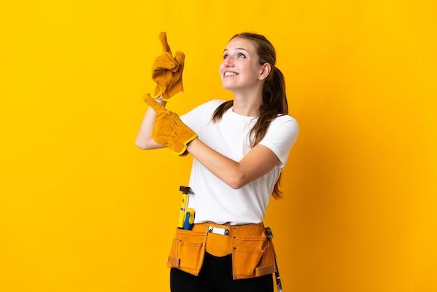 Junge elektrikerin lokalisiert auf gelbem hintergrund, der mit dem zeigefinger eine große idee zeigt