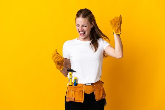 Junge elektrikerin lokalisiert auf gelber wand, die einen sieg feiert