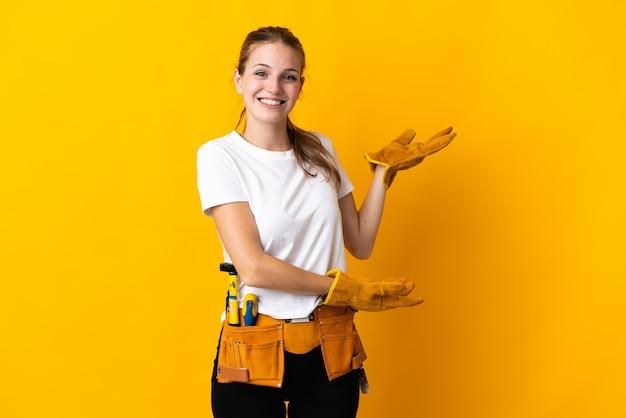 Junge elektrikerin lokalisiert auf gelber wand, die hände zur seite für einladung zum kommen ausdehnt