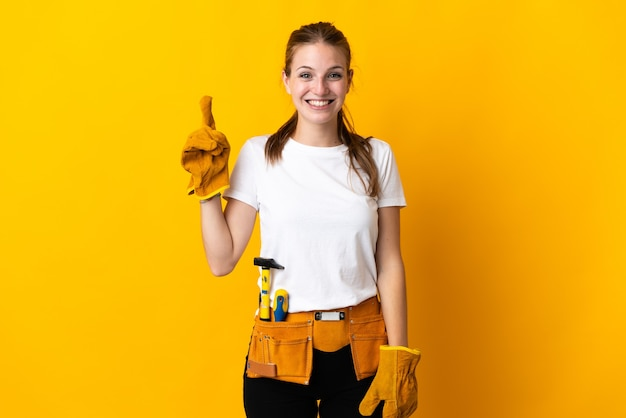 Junge elektrikerin lokalisiert auf gelber wand, die mit dem zeigefinger eine große idee zeigt