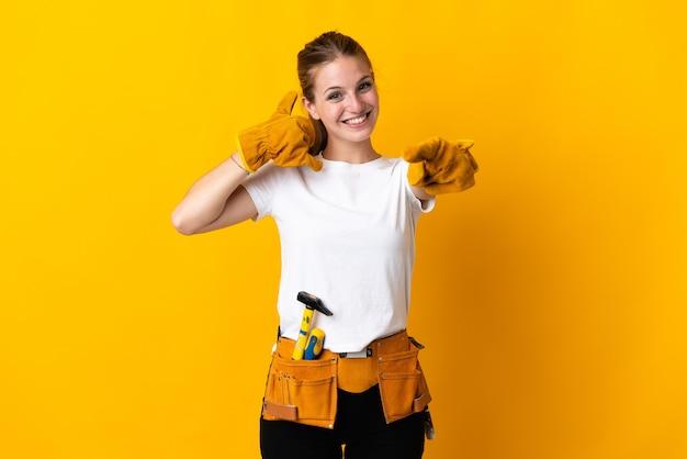 Junge elektrikerin lokalisiert auf gelber wand, die telefongeste macht und front zeigt