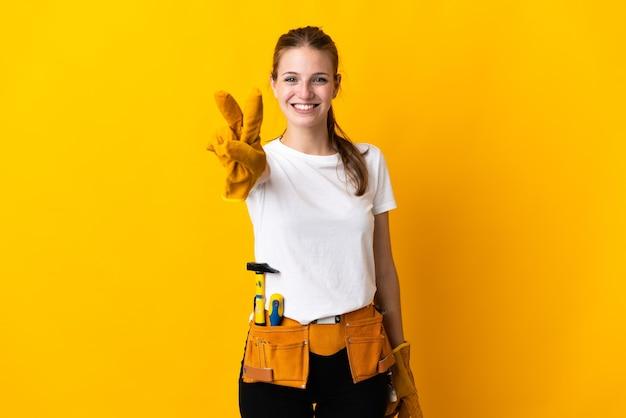 Junge elektrikerin lokalisiert auf gelber wand lächelnd und siegeszeichen zeigend
