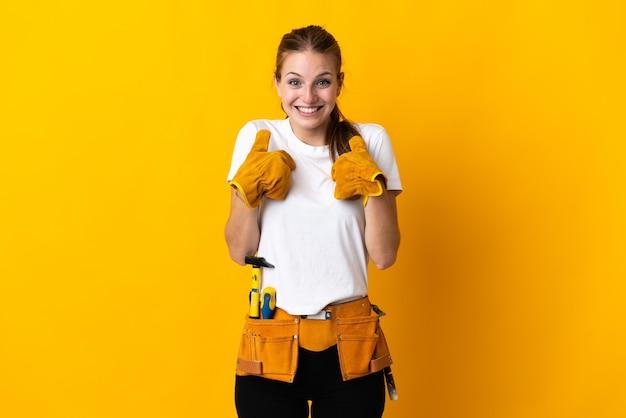 Junge elektrikerin lokalisiert auf gelber wand mit überraschungsgesichtsausdruck