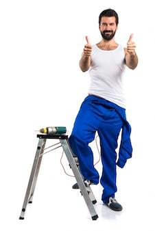 Junge elektrotechniker mit einem bohrer mit daumen nach oben