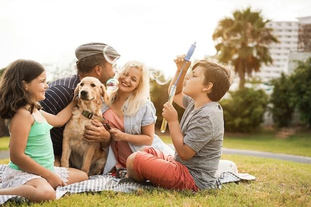 Junge eltern, die im sommer spaß mit kindern und ihrem haustier im park im freien haben