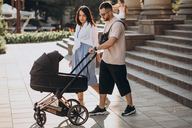 Junge eltern, die mit ihrem baby in einem kinderwagen gehen