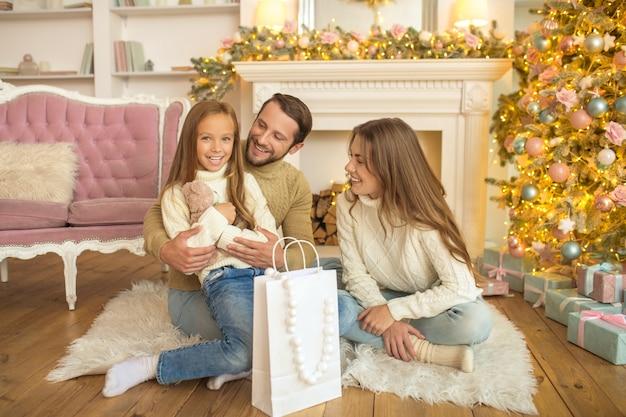 Junge eltern geben ihrer tochter weihnachtsgeschenk