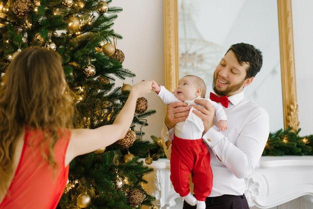Junge eltern mit einem kleinen kind schmücken den weihnachtsbaum zu weihnachten
