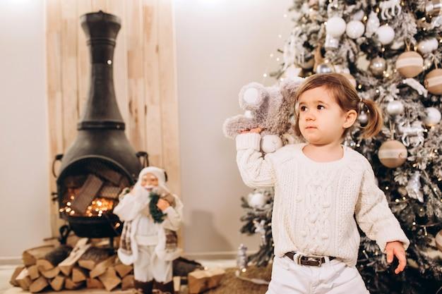 Junge eltern mit einer kleinen tochter in der nähe des weihnachtsbaumes