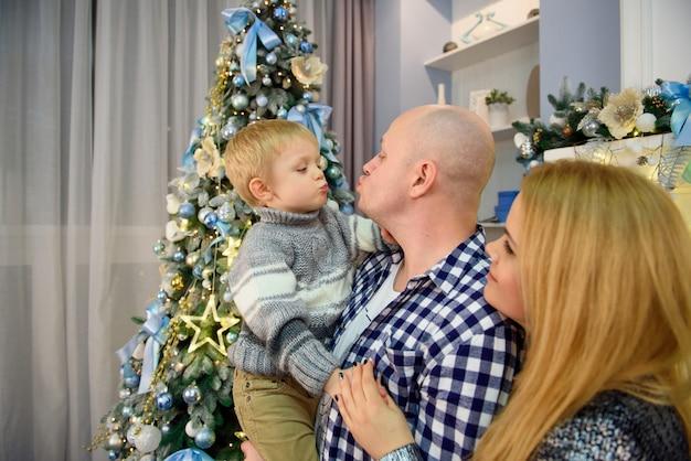 Junge eltern mit ihrem sohn, der in die kamera lächelt, während weihnachten feiert.