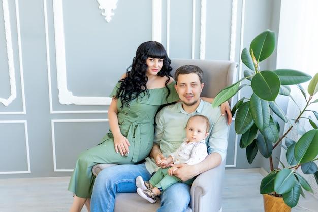 Junge eltern umarmen ihr baby in einem hellen raum in grüner kleidung, glückliches familienkonzept, familientag