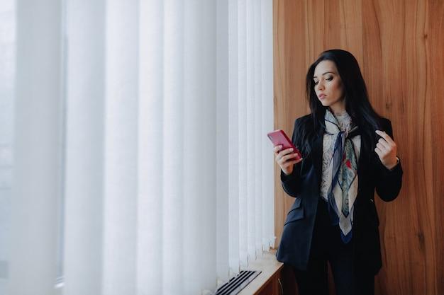 Junge emotionale attraktive frau in der geschäftsart kleidung an einem fenster mit einem telefon
