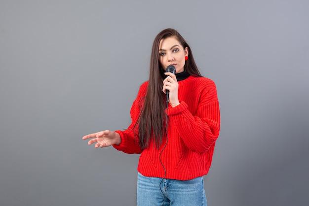 Junge, emotionale brünette mit einem mikrofon in einem roten pullover singt karaoke oder sagt eine rede, isoliert auf grau