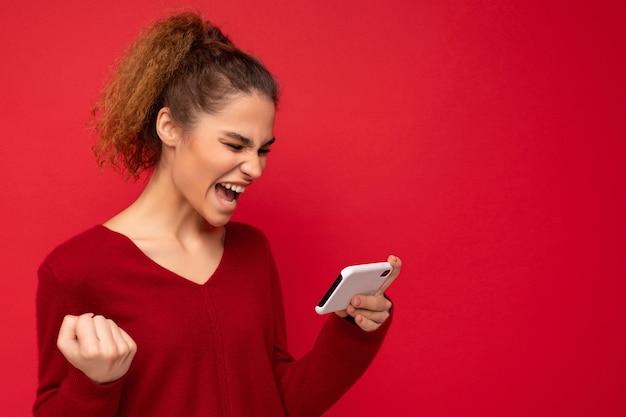 Junge emotionale frau, die smartphone hält
