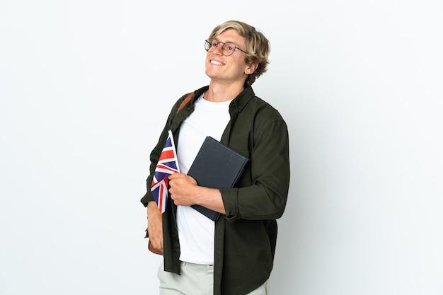 Junge englische frau, die eine britische flagge hält, die mit armen an der hüfte aufwirft und lächelt