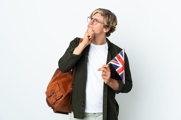 Junge englische frau, die eine britische flagge hält und nach oben schaut