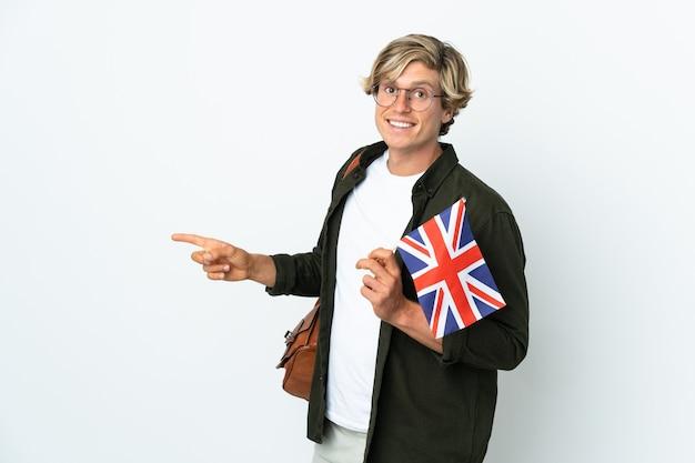 Junge englische frau, die eine flagge großbritanniens hält, die finger zur seite zeigt