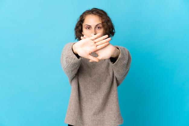 Junge englische frau lokalisiert auf blauem hintergrund, der stoppgeste mit ihrer hand macht, um eine handlung zu stoppen